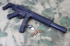 Submachine gun MP5 with silencer on camouflaged Stock Photos