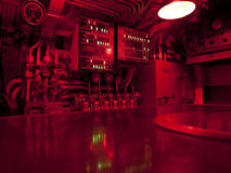 Submarine Command Center. The command center of a WWII submarine illuminated with red lights to enable clear vision at night or day while running underwater Royalty Free Stock Photos