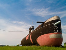 Submarine on green field. Surreal image of old steel submarine on a green field royalty free stock photo