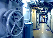 Submarine interior. Toned in blue, focus on the lock wheel Royalty Free Stock Image