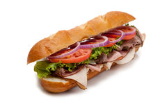 Submarine sandwich on a white background. A submarine sandwich including ham, turkey, roast beef, tomato, lettuce, onion and cheese on a french bun on a white Royalty Free Stock Images
