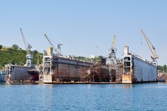Submarine and ship under repairing by technical team in floating dry docks stock image