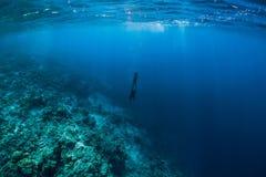Submarino libre del buceador en el océano con las rocas y el coral imagen de archivo
