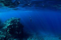 Submarino libre del buceador en el océano con las rocas y el coral fotos de archivo