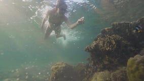 Submarino que nada de la mujer alegre entre pescados y el arrecife de coral exóticos en el mar Mujer joven en los vidrios que bu almacen de video