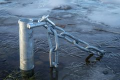 Submerged pole with chain in icy water stock photos