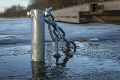 Submerged pole with chain in icy water stock images
