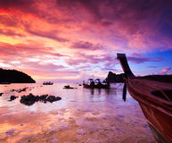 Submerged rocks and long tail boat in the sunset Royalty Free Stock Photo