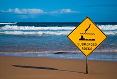 Submerged rocks sign on the beach Royalty Free Stock Images