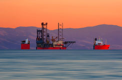 Submerging cargo ship. A cargo ship loaded with a juck-up rig Stock Images