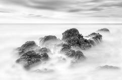 Submersão das rochas em um oceano do céu, paisagem preto e branco da praia fotos de stock royalty free