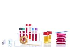 Submeta com sangue de diversos tubos, placas petri e as amostras de urina do fundo no laboratório Fotos de Stock Royalty Free