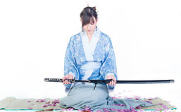 Submissive geisha in blue kimono with katana Royalty Free Stock Images