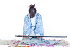 Submissive geisha in blue kimono with katana Royalty Free Stock Image