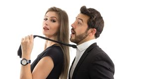 Wife pulls her husband by the tie. She is smiling. Submissive husband.. stock photography