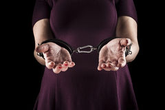 Submissive woman wearing a purple dress in leather handcuffs on. Black background royalty free stock images