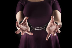 Submissive woman wearing a purple dress in leather handcuffs on. Black background stock photos