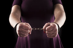Submissive woman wearing a purple dress in metal handcuffs on bl Stock Photography