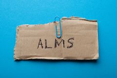 Submit alms, concept. Old torn cardboard on a blue background.  royalty free stock photos