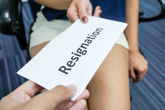 Submit a resignation letter. A woman submit a resignation letter to the boss Stock Photo