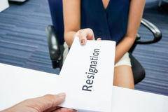 Submit a resignation letter. A woman submit a resignation letter to her boss Stock Images