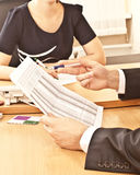 Subordinate makes a report. On a piece of paper to your boss sitt Stock Photo
