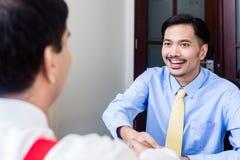 Subordinate professional talks to supervisor in office building. Indonesian subordinate business professional talks to supervisor in office Stock Photo