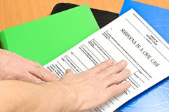 Subpoena. On colored folders is blank subpoena. On top of the man`s hand Royalty Free Stock Photography