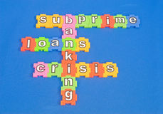Subprime mortgage loans. A macro image of the words subprime loans and the banking crisis in colorful lower case letters composed of jigsaw pieces on a blue Stock Image