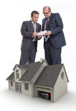 Subprime. Two men signing a document and a house rendering Royalty Free Stock Photography
