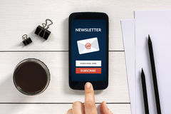 Subscribe newsletter concept on smart phone screen with office o Stock Image