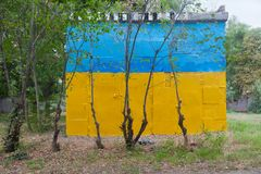 Subsidiary building painted in colors of the Ukrainian flag behi. Nd young trees in the city of Kherson, Ukraine Stock Photo