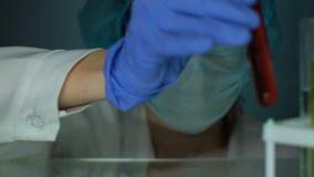 Substância oleosa do gotejamento do técnico de laboratório no tubo de ensaio com a amostra líquida vermelha video estoque