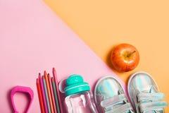 Substance d'étude de clothesand d'enfants : sneackers, crayons, bouteille de l'eau et montres de généralistes d'électron photographie stock libre de droits
