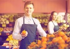 Substance dans le tablier vendant les oranges douces, les citrons et les mandarines Image stock