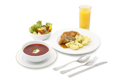 Substantial dinner. Soup with potato, meat, fresh salad and juice on white background Stock Photos