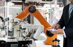 Substituição esperta 4 industriais do robô 0 do braço e do homem futuros do robô da tecnologia das coisas que usa o controlador fotografia de stock royalty free