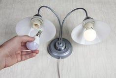 Substituindo ampolas elétricas na lâmpada de parede do agregado familiar, ampola do diodo emissor de luz Imagens de Stock Royalty Free