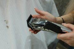 Substituindo o bocal de uma tosquiadeira de cabelo el?trica As m?os mudam proveem de bocal tosquiadeiras de cabelo el?tricas fotografia de stock