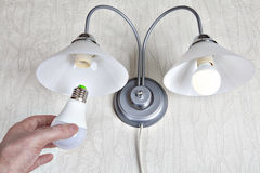 Substituindo os bulbos em luzes da parede, a mão guarda a lâmpada do diodo emissor de luz Imagem de Stock