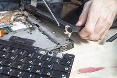 Substituindo a tela do portátil O técnico do serviço desaparafusa o parafuso que guarda a dobradiça O teclado removido é ao lado  fotografia de stock