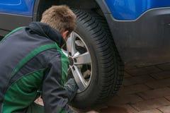 Substituya los neumáticos del verano contra los neumáticos del invierno Foto de archivo