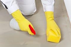 Substrato limpio del cemento del trabajador con la esponja Foto de archivo