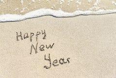 Subtítulo de la Feliz Año Nuevo en la arena de la playa del mar con la onda Fotografía de archivo libre de regalías