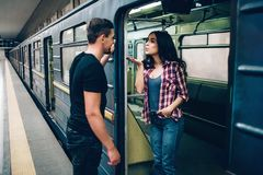 Subterr?neo do uso do homem novo e da mulher Pares no metro A jovem mulher bonita envia beijos para equipar Olhar do indiv?duo no imagens de stock royalty free