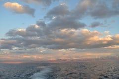 Subtile Wolken über dem Seehorizont und den Gebirgsketten Lizenzfreies Stockbild
