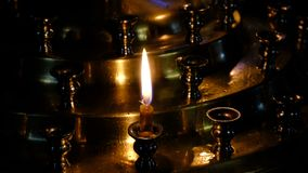 Subtle church candles burn. In an Orthodox Christian church near holy images in the dark in high resolution 4k stock footage