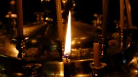 Subtle church candles burn. In an Orthodox Christian church near holy images in the dark close-up, filmed using zooming and moving the camera stock video