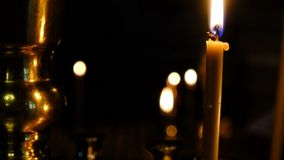 Subtle church candles burn. In an orthodox christian church near holy images in the dark close-up, filmed using zooming and moving the camera stock footage