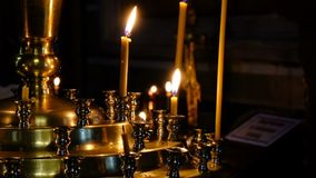 Subtle church candles burn. In an Orthodox Christian church near holy images in the dark close-up, filmed using zooming and moving the camera stock video footage